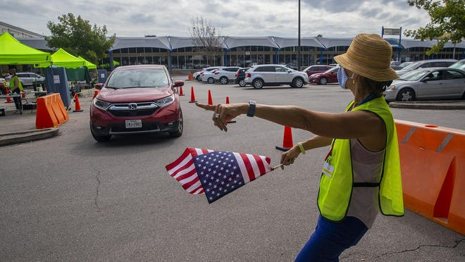Clerk Judy Gressel directs traffic in the parking lot as voters make their way to the Austin drive-thru ballot drop-off location at 5501 Airport Blvd. on Thursday.
