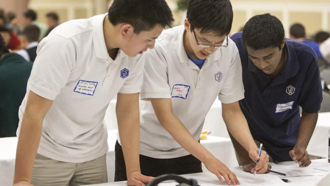 Charter School of Wilmington mathletes Miles Wang (from left), Zhiyuan Liu and Vickram Rajendran work through team questions on March 31.
