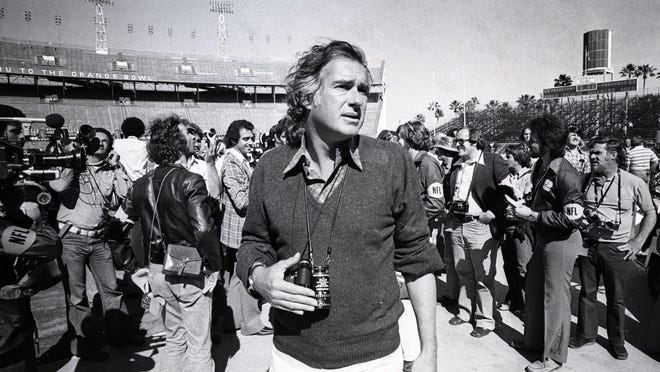 January 29, 1977: Director John Frankenheimer stands among news photographers at the Orange Bowl in Miami during the filming of the movie, 'Black Sunday.' Real news photographers were recruited as extras to pretend to be shooting Super Bowl X, and then to turn and photograph the crowd fleeing the stands, as the blimp crashes into the Orange Bowl.