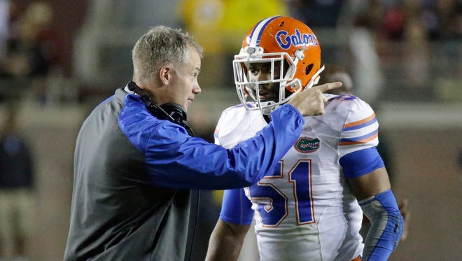 FILE - In this file photo from Nov. 29, 2014, Florida defensive coordinator, D.J. Durkin talks with linebacker Michael Taylor (51) during the second half of an NCAA college football game against Florida State in Tallahassee, Fla. Durkin, whose name has been tied to a number of defensive coordinator jobs, notably Texas A&M, is among five interim coaches who will be in charge of teams this bowl season. The others are Dave Baldwin at Colorado State, David Gibbs at Houston, Joe Rudolph at Pittsburgh and Barney Cotton at Nebraska. (AP Photo/John Raoux, File)