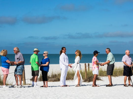 Couples recite their vows together during the 9th Annual Vow Renewal Ceremony at Lovers Key State Park on Wednesday, Feb. 14, 2018.