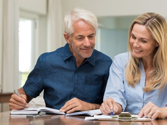 mature-couple-discussing-finances-with-pens-and-paper_large.jpg