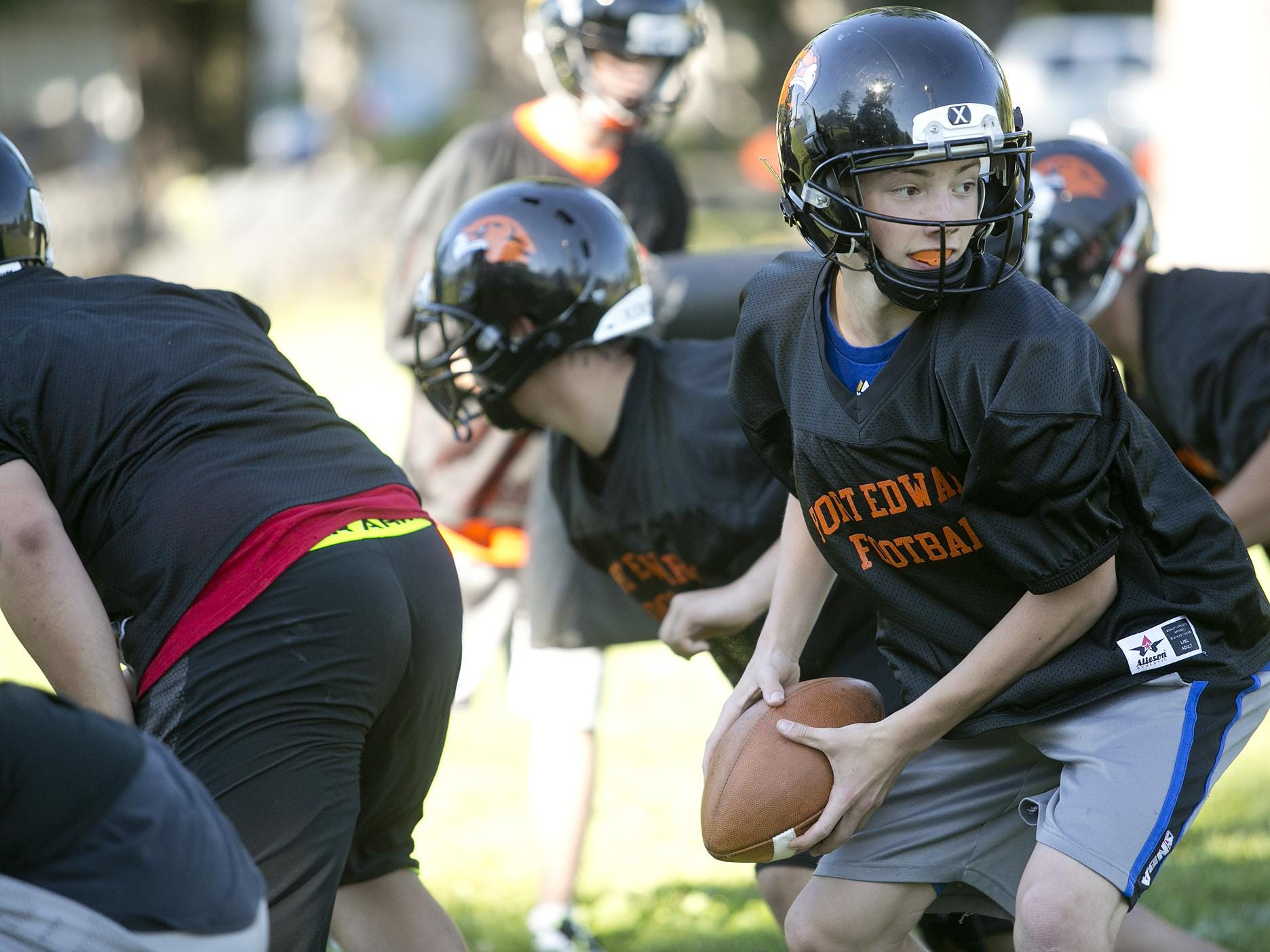Quarterback Ian Gibbs looks to hand off the ball during the first day of football practice at John Edwards High School, Tuesday, Aug. 4, 2015.