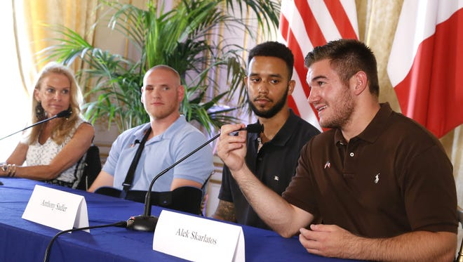U.S. ambassador to France Jane Hartley sits with Spencer Stone, Anthony Sadler and Alek Skarlatos during a news conference at the U.S. Embassy in Paris on Aug. 23, 2015.