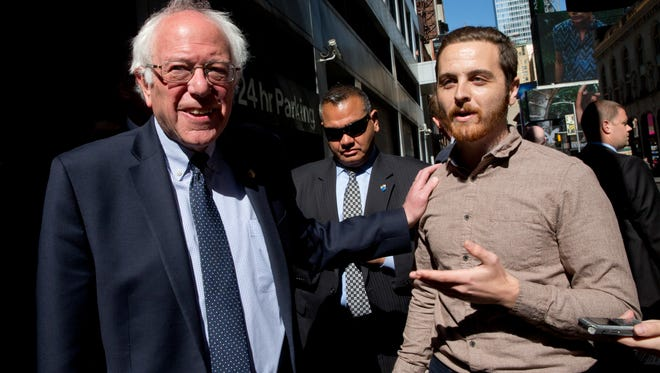 Democratic presidential candidate Sen. Bernie Sanders, I-Vt., speaks to supporter Michael Cantalupo who said he is unable to vote in the New York primaries while taking a walk in New York's Times Square, April 19.