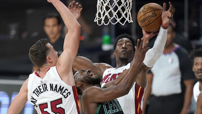The Miami Heat's Duncan Robinson, left, and Bam Adebayo defend against a shot attempt by the Celtics' Kemba Walker during the second half of the Eastern Conference Finals Game 1 Tuesday in Lake Buena Vista, Fla.