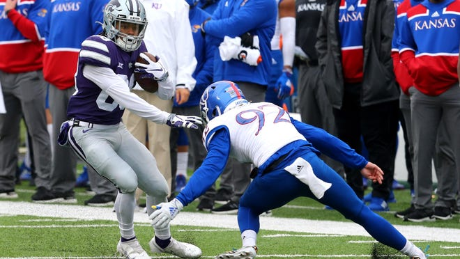 Kansas punter Donovan Gagen, right, attempts to tackle Kansas State returner Phillip Brooks during Saturday's game at Bill Snyder Family Stadium in Manhattan. Brooks had a pair of return touchdowns and a total of four 40-plus-yard punt returns in the No. 20-ranked Wildcats' 55-14 victory over the Jayhawks.