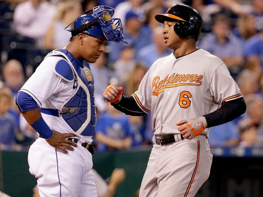 Baltimore Orioles' Jonathan Schoop (6) runs past Kansas City Royals catcher Salvador Perez to score after hitting a two-run home run during the fourth inning of a baseball game Wednesday, Aug. 26, 2015, in Kansas City, Mo. (AP Photo/Charlie Riedel)