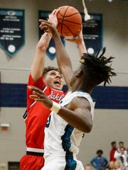 Oakland's Keishawn Davidson (0) and Siegel's Jones Franklin Jr. (3) both go after a rebound on Tuesday.