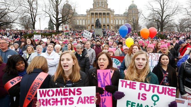 Ellie Hildebrandt, 15 (from left), Barb Hildebrandt and Emma Hildebrandt, 16, all of Des Moines, chant together with the crowd Saturday, Jan. 21, 2017 as they get ready to march around the capitol building at the Iowa Women's March in Des Moines. Thousands of people rallied and marched in Iowa in a show of support for the national Women's March on Washington.