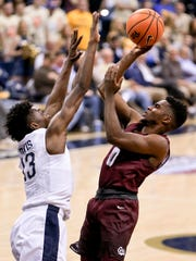 Montana's Michael Oguine (0) shoots over Pittsburgh's Khameron Davis (13) in the second half of an NCAA college basketball game in Pittsburgh in the fall of 2017. (AP Photo/Keith Srakocic)