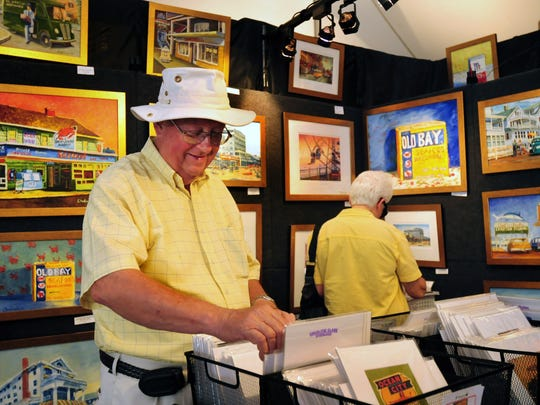 Garen Mortensen, left, and his wife, Claudine, of Berlin look at paintings and prints in the Charlene Clark Studio booth at the 36th annual Sunfest in Ocean City.