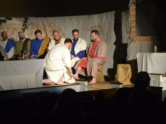 "Jesus of Nazareth, portrayed by Chris Rossmiller, kneeling on right, washes the feet of his 12 disciples during the annual reenactment of ""The Living Last Supper."""