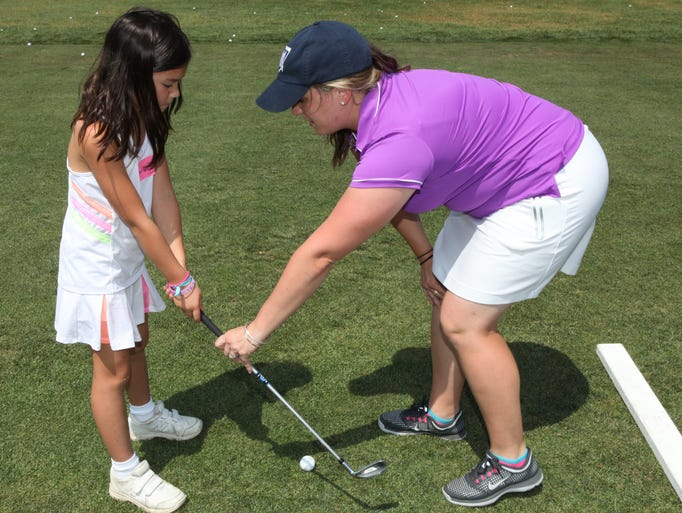 Charlotte Oh, 7, gets expert help from golfer Christina Doyle at the Girls to the Tee Clinic, a golf clinic for girls held at the Westchester Country Club in Harrison Aug. 11, 2014.