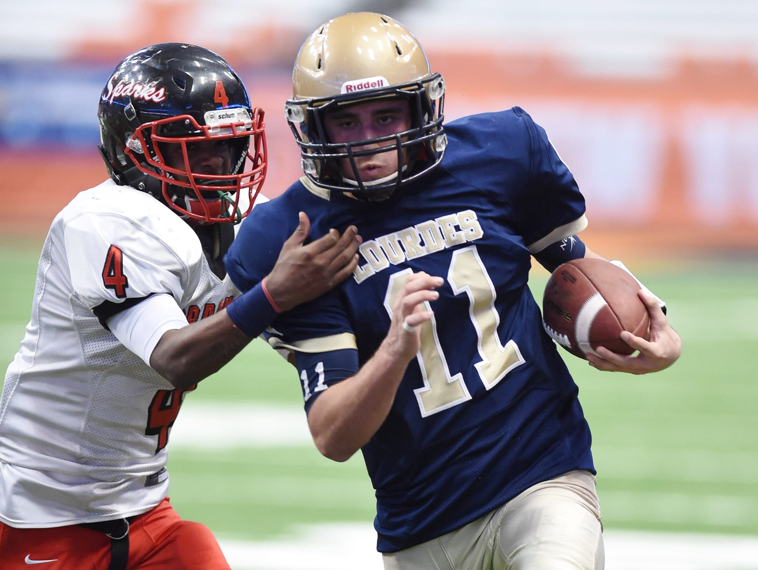 Lourdes' Dean Rotger runs the ball ahead of South Park's Leelan Coleman during the New York State Championship final in Syracuse on Friday.