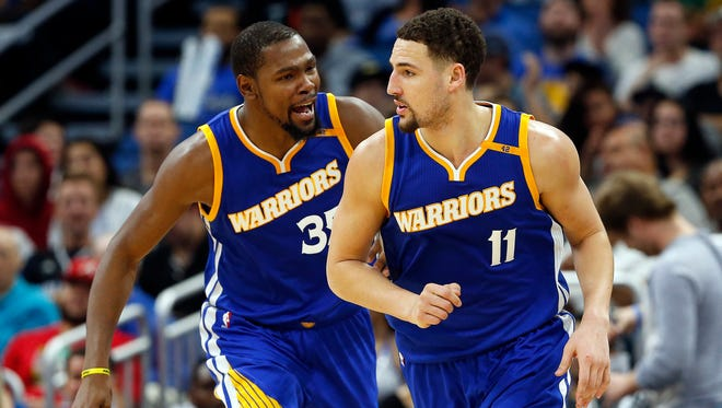 Golden State Warriors forward Kevin Durant (35) congratulates guard Klay Thompson (11) during the second half at Amway Center.