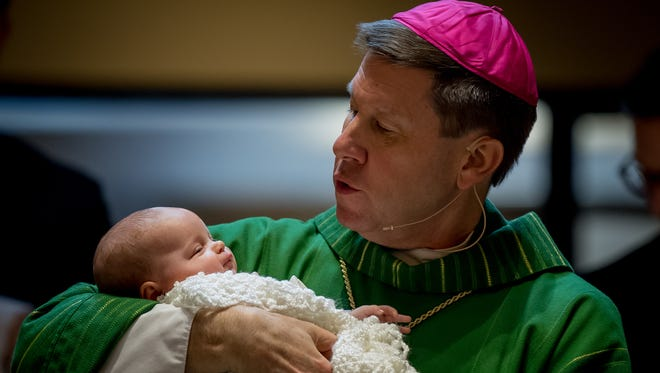 Bishop J. Mark Spalding holds a baby he has just baptized while celebrating his final Mass at Holy Trinity Catholic Church in Louisville, Ky., on Jan. 14, 2018. Spalding is leaving Louisville to become bishop in the Diocese of Nashville.