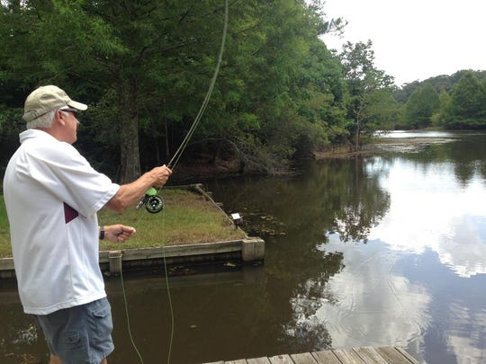 """Glenn """"Catch"""" Cormier fly fishes from his dock, trying to catch a fish from an extension of Cotile Lake."""