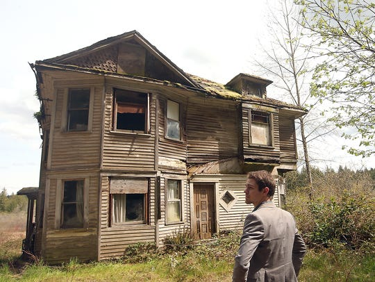 Michael Bowes of Strategy Real Estate walks around a dilapidated home in Seabeck on Thursday. He is listing the home, which is on a large property with a wetland, that has failed to sell during previous attempts.