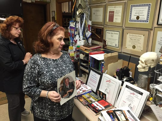 Susan Levine and Jan Johnson review forensics memorabilia from Philip Levine's career at his Pensacola office.