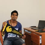 Guillaume Sauter, an international student from Paul Sabatier University, shows off his school spirit as he sits at his desk in his dorm room at Hercules community.