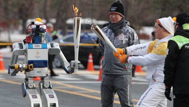 A DRC-Hubo robot prepares to light the torch of bearer Dr. Dennis Hong, a professor at the University of California, Los Angeles, during the Olympic Torch Relay in Daejeon, South Korea. The 2018 Pyeongchang Winter Olympics will be held from Feb. 9 to 25, 2018, in South Korea.