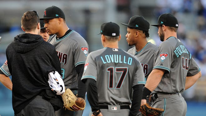 April 14, 2018; Los Angeles, CA, USA; Arizona Diamondbacks manager Torey Lovullo (17) and the team trainer meet with starting pitcher Taijuan Walker (99) during a stoppage in play in the second inning at Dodger Stadium.