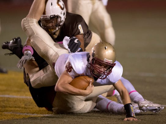 Mater Dei's Cole Happe (4) is sacked by both Central's