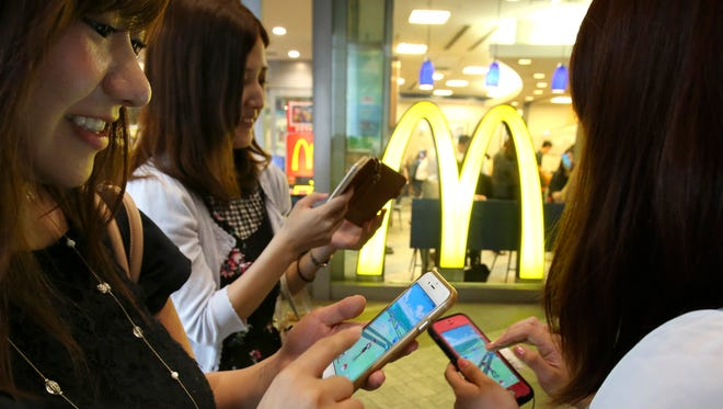 """Women play """"Pokemon Go"""" in front of a McDonald's restaurant in Tokyo, Friday, July 22, 2016.  The Japan launch of """"Pokemon Go"""" on Friday included the game's first partnership with an outside company: fast-food giant McDonald's."""