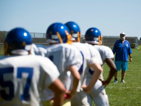 Defensive coordinator Dave Marvel lines up players as the varsity team practices in Gerogetown.