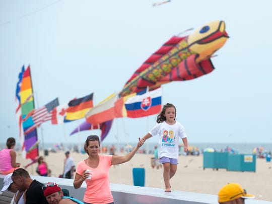 Kites soar over a crowded beach and Boardwalk Thursday afternoon.
