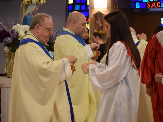 Taylor Amarando, 19, of Sicklerville receives Communion from Bishop Dennis J. Sullivan during the St. Joseph High School Class of 2016 Baccalaureate Mass on May 31.