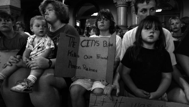 MAY 14, 1992: Residents of Lower Price Hill pack Cincinnati City Council chambers Wednesday, May 13, 1992. Council earmarked $30,000 to tear down vacant building where the body of 10-year-old Aaron Raines was found. Pictured left to right: Kim Saylor, Shawn Hawkins holding Josh Johnson, 2, Diane Gribbins, Amy Gumm with Amy Offenbacker in front (far right).