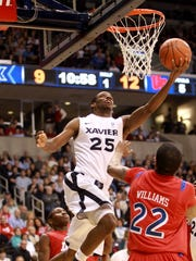 Xavier's Dante Jackson (25) goes up for a shot against Dayton Paul Williams (22) in the first half of a game against the University of Dayton on Saturday January 15, 2011 at the Cintas Center.