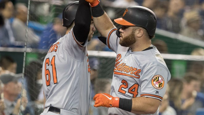 Baltimore Orioles DJ Stewart, right, is greeted by Austin Wynns after Stewart hit a two-run home run against the Toronto Blue Jays during the sixth inning of a baseball game Tuesday, Sept. 24, 2019, in Toronto. (Fred Thornhill/The Canadian Press via AP)