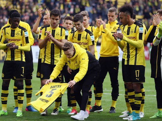 Marco Reus lays down the jersey of injured teammate