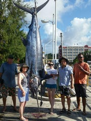 In this file photo, Capt. Gie Clark, left, and Jun Santos, right, and a family visiting from South Korea stand next to a 509-pound Pacific blue marlin they caught a few miles west of Guam.