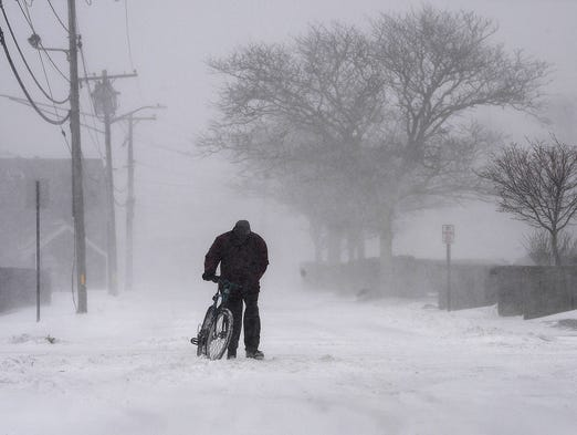 A person walks his bicycle through a snowstorm on March 26 in Hyannis, Mass. A storm blanketed the area with up to 6 inches of snow.