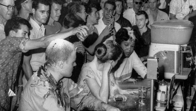 In this May 28, 1963 file photograph, a group of white people pour sugar, ketchup and mustard over the heads of Tougaloo College student demonstrators at a sit-in demonstration at a Woolworth's lunch counter in downtown Jackson, Miss. Seated at the counter, from left, are Tougaloo College professor John Salter and students Joan Trumpauer and Anne Moody. Anne Moody, a  civil rights activist who wrote about challenging segregation in the South is being honored in her hometown, two years after her death.