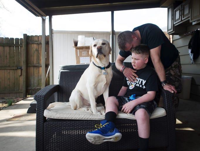 Bill Kohler comforts his son, Ayden Ziegler-Kohler,