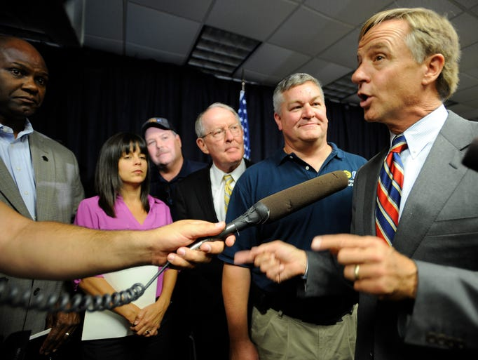 Tennessee Gov. Bill Haslam talks to the media as they crowd around speakers after GM announced Wednesday, Aug. 27, 2014, it will build the next-generation Cadillac SRX at its big Spring Hill plant and will invest another $185 million for new engines to be built at the complex, retaining 390 jobs.