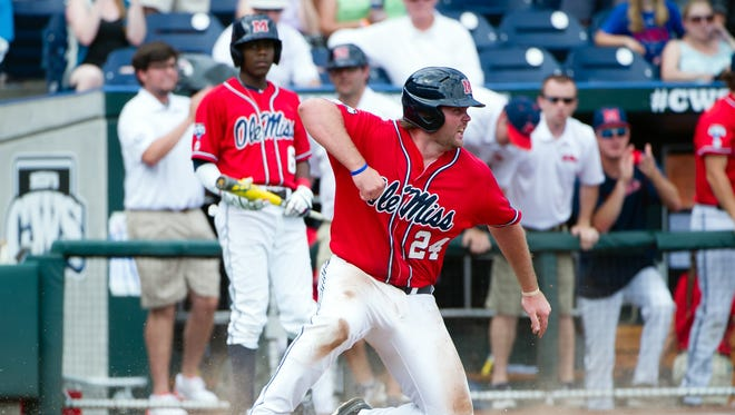 Ole Miss infielder Sikes Orvis (24) scores the first run of the game in the seventh inning against the Texas Tech Red Raiders during game seven of the 2014 College World Series at TD Ameritrade Park Omaha. Mandatory Credit: Steven Branscombe-USA TODAY Sports
