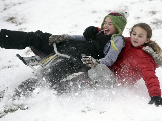 Stella Knipp and Kylee Lowery, both age 10, go sledding