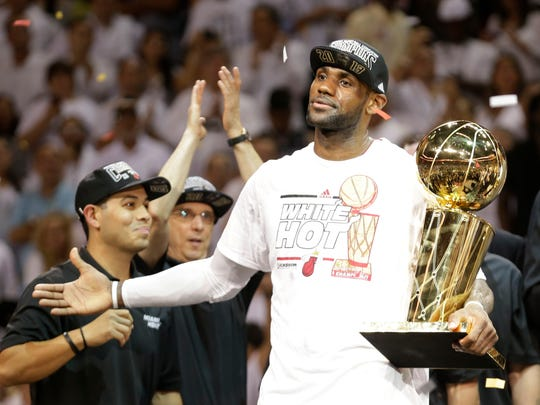 Miami Heat's LeBron James holds the the Larry O'Brien NBA Championship Trophy after Game 7 of the NBA basketball championship against the San Antonio Spurs, June 21, 2013, in Miami.