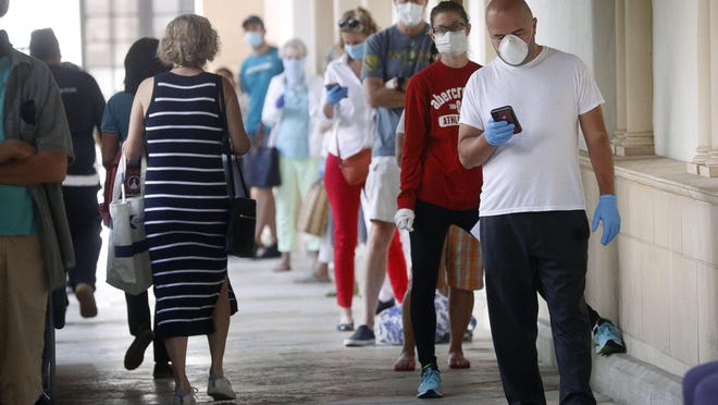 Customers of Publix Palm Beach form a line along the north side of the store's entrance. Spaces on the ground have been marked off with blue tape to ensure they remain 6 feet apart while waiting to enter, Thursday, April 9, 2020.