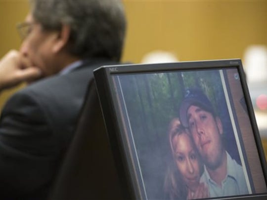 A photo of Jodi Arias and her former boyfriend, Travis Alexander, is shown on a computer screen during the Arias' sentencing retrial.  phase of the Arias' retrial at Maricopa County Superior Court, Tuesday, Feb. 24, 2015 in Phoenix. Prosecutors showed a photo of Alexander's slit throat.