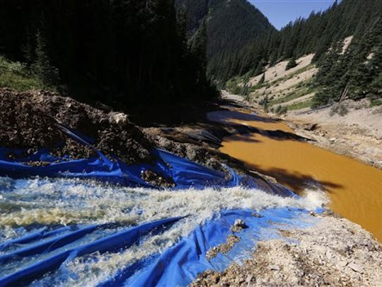 Water flows on Aug. 14 through a series of sediment retention ponds built to reduce heavy metal and chemical contaminants from the Gold King Mine waste water spill in the spillway about one-fourth of a mile downstream from the mine north of Silverton, Colo.