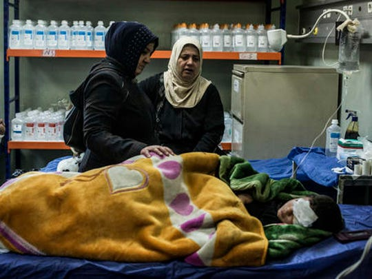 The mother and aunt of a boy wounded in a car bomb attack in the district of Gogjali in Mosul comfort him in a hospital in Irbil, Iraq, Thursday, Dec. 22, 2016.