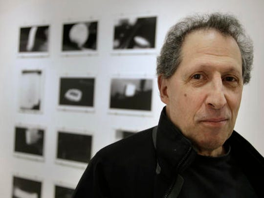 """In this Wednesday, Feb. 22, 2017 photo, photographer Karl Baden, of Cambridge, Mass., stands for a photo in front of an exhibit of his photographs from 1976 called """"Thermographs,"""" at the Miller Yezerski Gallery, in Boston. On Feb. 23, 1987, long before they were called selfies, Karl Baden snapped a simple, black and white photo of himself. Then he repeated it, every day, for the next three decades. Baden's """"Every Day"""" project turns 30 years old Thursday, Feb. 23, 2017."""