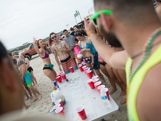 Spring breakers play a game of beer pong on beach in